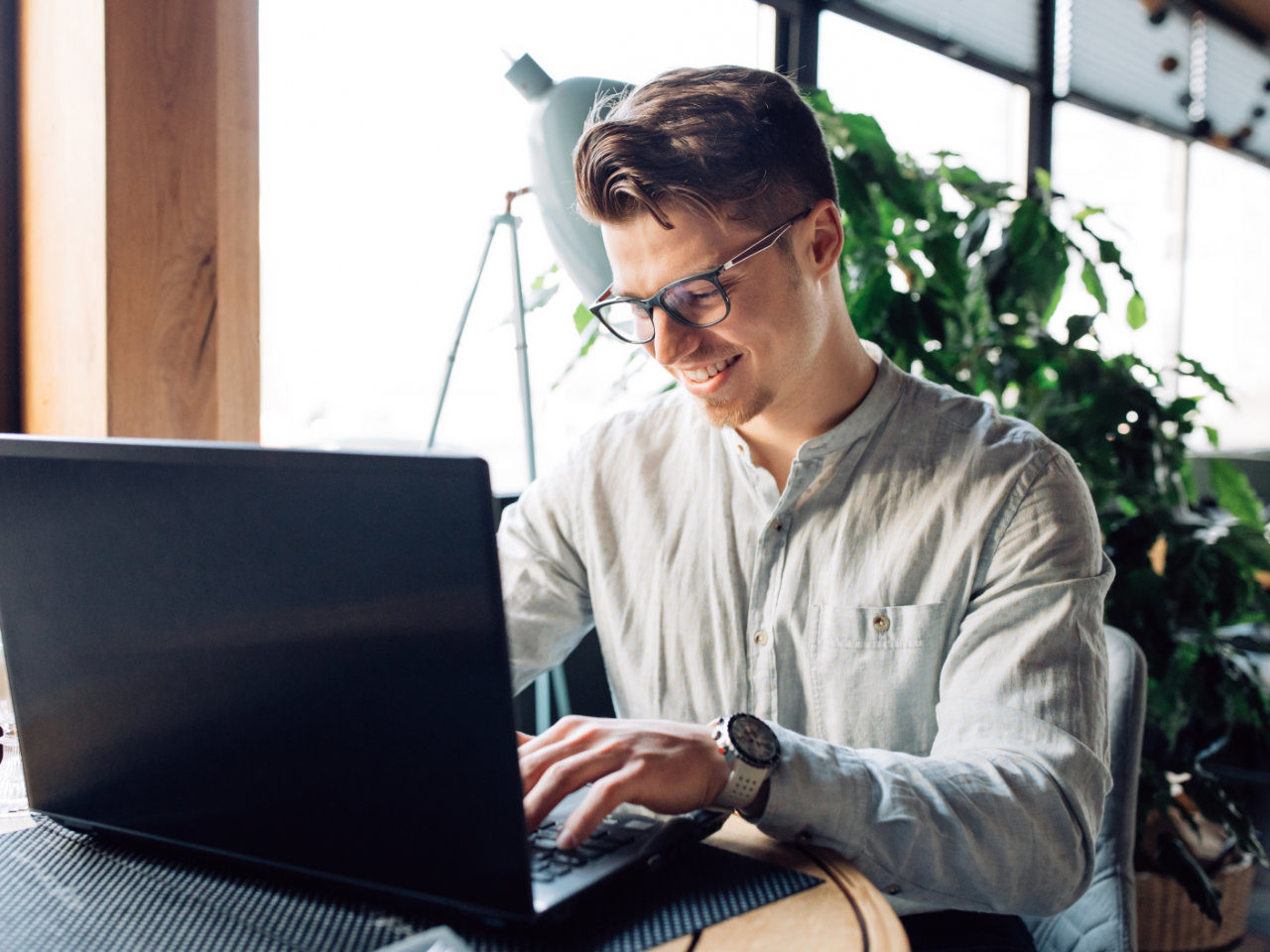 Attractive smiling businessman in eyeglasses working on laptop, typing, spending time at cafe. Dressed in white shirt.